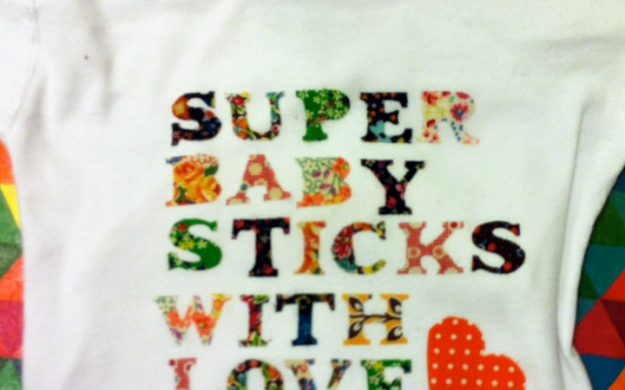 "White onesie with ""super baby sticks with love"" in a patchwork of fabrics cut into letters, punctuated by a red heart."