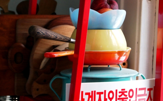 Red metal Ikea shelf holds a robin egg blue Dans pot, flame orange Le Creuset pan, wood handled pale yellow enamel pot, and semi-transluscent blue glass bowl. Korean sign in foreground, assorted wood cutting boards in background.