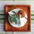 Birds-eye view of table accoutrements--mortar and pestle, salt cellar, sugar bowl, salt and pepper shakers, plant in antique bottle--on a white plate on a teak tray on a striped woven runner in shades of green and white.