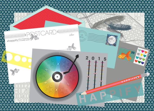 The 2015 happify calendar cover is a desktop with a transparent rulers, pencil, blotter, feathers, envelopes, stamps, and a color version of November, which is a rainbow record playing.