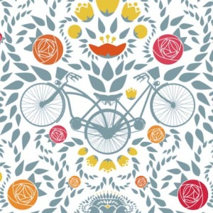 Up close look at the bikes in the pattern, with their shared back wheel, joined saddles, and other details. Flowers and leaves/hops in oranges and pinks around.