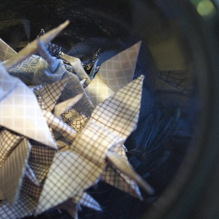 A shot of a tangle of happify's security envelope paper cranes shot from inside their blue glass bell jar, focus on partially buried crane, reflections of others on interior glass.