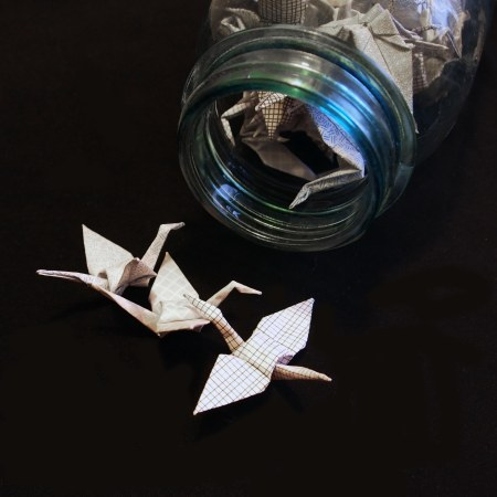 Picture of three of happify's security envelope origami paper cranes spilling out of a blue glass bell jar against a black background.