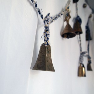 A close-up of one of the etched bells on the homemade twine garland, the others blurry in the background against the white shower curtain.