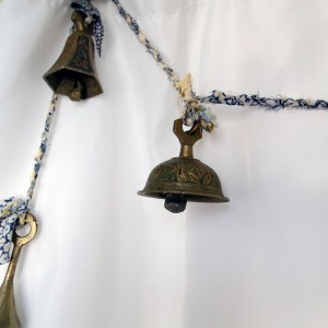 A close-up of a carved and painted brass bell, on blue and cream/white homemade rope.