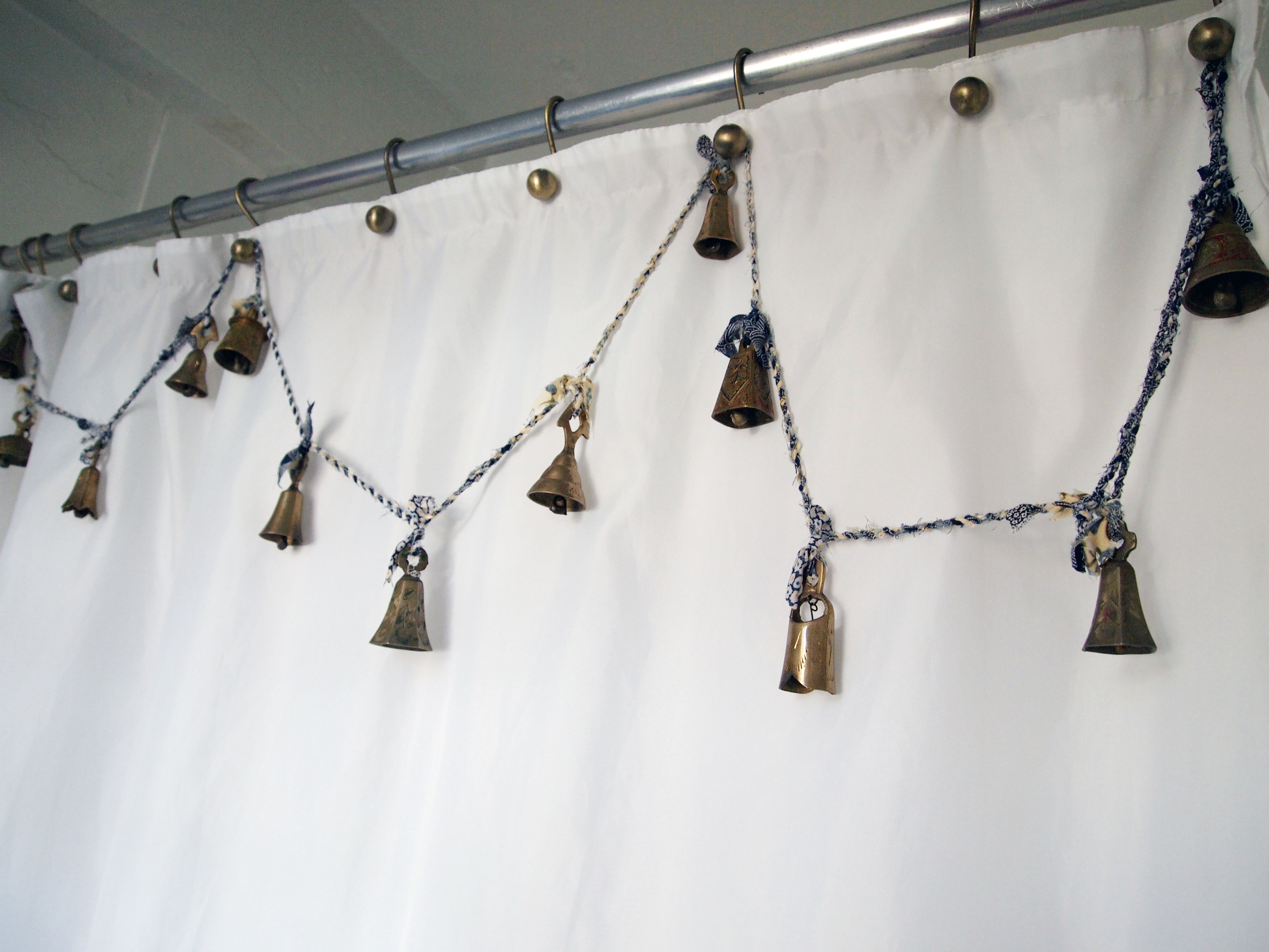 Brass Bells Hang From Brushed Brash Shower Curtain Hooks On A DIY Blue And White Homemade