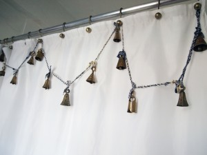 Brass bells hang from brushed brash shower curtain hooks on a DIY blue and white homemade twine garland.