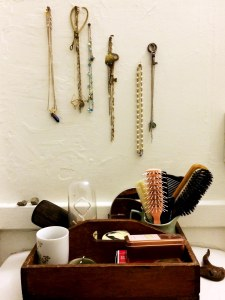 A selection of necklaces and chains, plus antique keys and tools, hang above pyrite/fool's cold, brushes and combs, an acrylic penguin filled with used matchsticks, vintage brush, candle, and other accessories of a bathroom.
