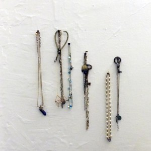 An assortment of necklaces (crystal, tazanite, labradorite, vintage pearls, brass tetrahedrons, crystal, silver, etc.) as well as vintage keys and caliper hang from small upholstery nails positioned in the Big Dipper constellation form on a plain white plaster wall.