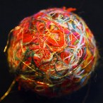 A close-up of a vibrant happify thread ball against a black backdrop shows an overlapping network of intertwined gold filaments over a tangle of cardinal red, orange, grey-blue, yellow, blue, magenta, forest green, salmon, pink, and other hues. A single blurry gold filament escapes from the nest in the foreground.