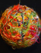 A photo of a newly designed happify thread ball pops against a black backdrop shows an overlapping network of interlaced gold lines over a nest of cardinal red, orange, grey-blue, yellow, blue, magenta, forest green, salmon, pink, and other rainbow colors.