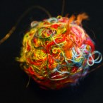 This shot of a colorful happify thread ball against a black backdrop highlights the criss-cross design of gossamer gold threads over a tangle of red, orange, yellow, blue, forest green, salmon, pink, and other hues. Blurred gold filaments escape from the tangle in the background.