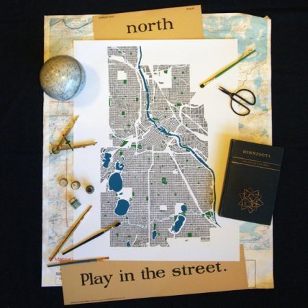 "The screenprinted happify Minneapolis map poster is framed by another Minnesota map, framed by a black background. On the maps are two vintage flashcards; the top one reads ""north"" and the bottom one reads ""Play in the street."" Scattered on the edges of the maps are additional items: a moon globe, a metal drafting compass, four small jars of paint, blue and brass and green colored paint brushes, a black iron scissors, a book entitled ""Minnesota,"" and a handmade happify brass triakis icosahedron."