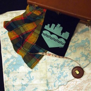 A folded black tshirt with a robin's egg blue screenprinted on black spills out of an antique caramel leather suitcase, along with a lumberjack flannel shirt, onto a map of the north woods of Minnesota, spotted with lakes. Atop the map and shirts curls a fabric measuring tape pulled partially out of its leather and brass case.