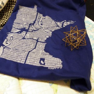 A screen-printed map of the city of Minneapolis in white, in the shape of the state of Minnesota, on a blue folded tshirt sits on a map of the Boundary Waters area. On top of the t-shirt is a polyhedron made of small brass pieces.