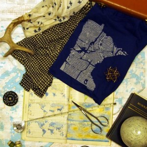 A tshirt with a screenprint of a map of Mpls in the shape of the state of Minn spills out of a vintage camel leather suitcase with two other items, one a silk scarf printed with blue birds and the other with a small geometric pattern of triangles. Scattered around them are a measuring tape, a globe of the moon, a scissors, a found antler, and a book on Minnesota, on top of a Japanese atlas, against a backdrop of the many lakes of the Boundary Waters area of the north woods.
