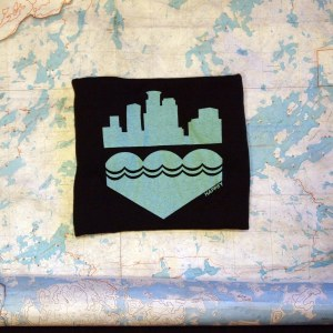 A folded black tshirt with a robin's egg blue screenprinted on black on a map of the Boundary Waters spotted with lakes.